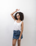 Happy woman doing victory sign. In front of a white wall, wearing glasses Royalty Free Stock Image
