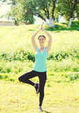 Happy woman doing yoga exercises on grass in summer day Stock Photo