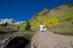 Happy Woman Doing Yoga at Maroon Bells. A happy woman practicing yoga in the scenic maroon bells in fall as a backdrop Royalty Free Stock Photos