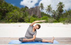 Happy woman doing yoga and stretching on beach. Fitness, sport and healthy lifestyle concept - happy woman doing yoga and stretching on mat over exotic tropical Royalty Free Stock Photography