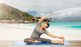 Happy woman doing yoga and stretching on beach. Fitness, sport and people concept - happy woman doing yoga and stretching on mat over exotic tropical beach Stock Photo