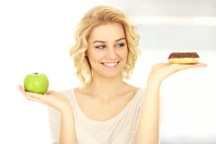Happy woman with donut and apple Stock Photography