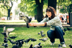 Happy woman with doves in park Royalty Free Stock Images