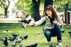Happy woman with doves in park Stock Photo