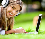 Happy woman downloading music Stock Image