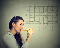 Happy woman drawing new house floor plan with pencil. Happy young woman drawing new house floor plan with pencil on gray wall background Royalty Free Stock Photo