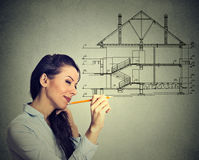 Happy woman drawing new house plan with pencil. Happy young woman drawing new house plan with pencil on gray wall background Stock Images