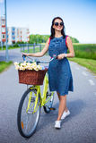 Happy woman in dress posing with vintage bicycle with basket Stock Photos