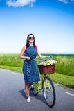Happy woman in dress posing with vintage bicycle with basket in Royalty Free Stock Image