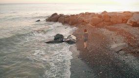 Woman walking beach at sunset stock footage