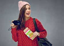 Happy woman dressed red knitted sweater holding camera, credit c. Ard with passport and tickets looking at side. Gray wall back Stock Image