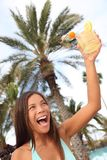 Happy woman with drink at tropical resort toasting. Beautiful mixed race caucasian / chinese young woman model having fun saying cheers Royalty Free Stock Photos