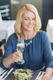 Happy woman drinking champagne at restaurant Royalty Free Stock Photography