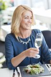 Happy woman drinking champagne at restaurant Royalty Free Stock Photo