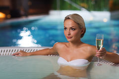 Happy woman drinking champagne at swimming pool Stock Photography