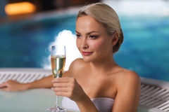 Happy woman drinking champagne at swimming pool Stock Photo