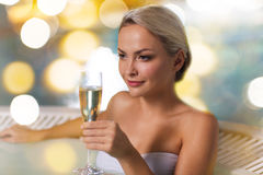 Happy woman drinking champagne at swimming pool Stock Images