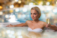 Happy woman drinking champagne at swimming pool Royalty Free Stock Photos