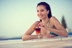 Happy woman drinking cocktail in pool Stock Image