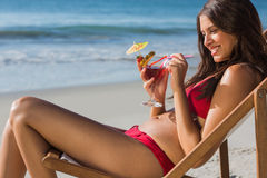 Happy woman drinking cocktail while relaxing on her deck chair Stock Image