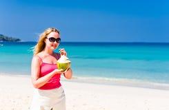 Happy woman drinking coconut milk on beach Stock Photo