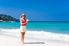Happy woman drinking coconut milk on beach Royalty Free Stock Image