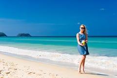 Happy woman drinking coconut milk on beach Stock Image