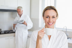 Happy woman drinking coffee in bathrobe Royalty Free Stock Image