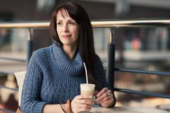 Happy woman drinking coffee in cafe Royalty Free Stock Photography