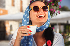 Happy woman drinking coffee In a cafe outdoors Stock Image