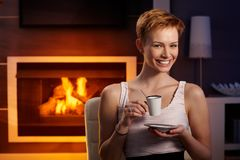 Happy woman drinking coffee by fireplace Stock Photos