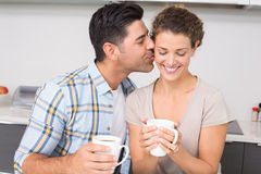 Happy woman drinking coffee getting a kiss from partner Stock Images
