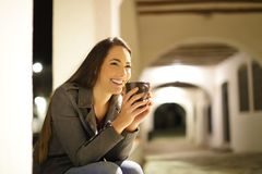 Happy woman drinking coffee sitting in a town street in the night stock image