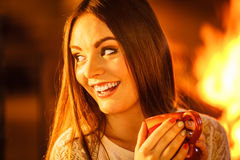 Happy woman drinking coffee relaxing at fireplace. Royalty Free Stock Images