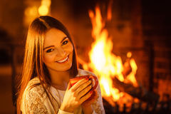 Happy woman drinking coffee relaxing at fireplace. Stock Photography