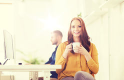 Happy woman drinking coffee or tea at office Royalty Free Stock Images