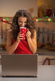 Happy woman drinking cup of chocolate and looking on laptop Stock Photos