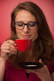 Happy woman drinking cup of coffee in early morning. Over red background Stock Image