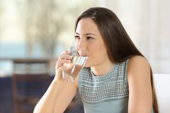 Happy woman drinking fresh water from a glass stock photo