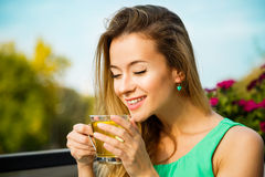 Happy Woman Drinking Green Tea Outdoors. Young Happy Woman Drinking Green Tea Outdoors. Summer Background. Shallow Depth of Field. Healthy Nutrition Concept Royalty Free Stock Photography