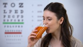 Happy woman drinking healthy fresh carrot juice, eyechart on background, vision. Stock footage stock video