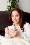 Happy woman drinking hot tea at home Royalty Free Stock Images