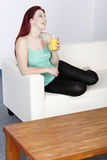 Happy woman drinking juice at home. Happy smiling young woman drinking fresh Orange juice at home on the sofa Stock Image