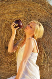 Happy woman drinking milk from cruse or crock. And hay as background Stock Image