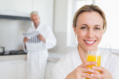 Happy woman drinking orange juice in bathrobe Royalty Free Stock Photography