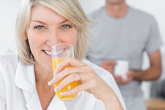 Happy woman drinking orange juice in kitchen Royalty Free Stock Image