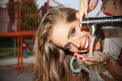 Happy woman drinking tap water. Pretty woman drinking water from the tap in the park royalty free stock images