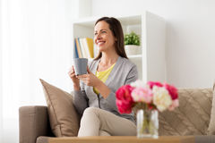 Happy woman drinking tea or coffee at home Stock Image