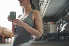 Happy woman drinking tea in kitchen stock photos