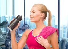 Happy woman drinking water from bottle in gym Royalty Free Stock Images